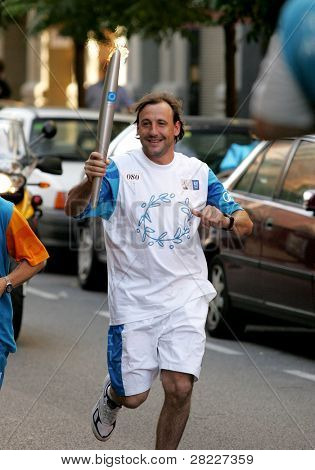 BARCELONA - JUNE 28: Spanish athlete Fermin Cacho carries the Athens 2004 torch during the Barcelona Torch Route through the city streets, June 28, 2004 in Barcelona, Spain