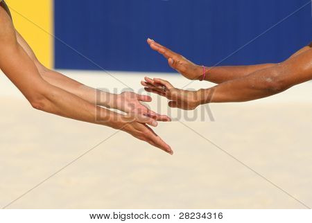 Hands of a beach volley players celebrating a point