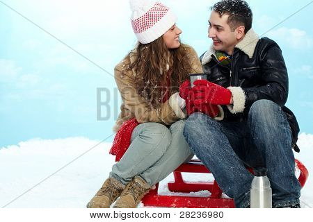 Portrait of amorous couple looking at one another while drinking hot tea on winter day