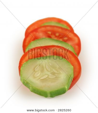 The Cut Slices Of A Tomato And A Cucumber.