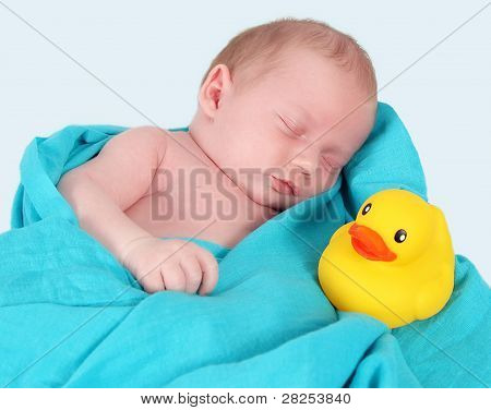 Sweet Newborn Sleeping Peacefully With Yellow Duckie. Isolated