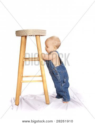 Little Boy in Coveralls Looking at a Stool