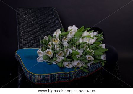 White Bouquet Of Tulips On Black Chair With Blue Cushion And Black Bra