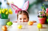 Happy Easter! Funny Child Girl With Rabbit Ears And  Eggs At Home In Kitchen poster