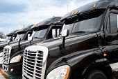 Fleet Of Black Semi-truck 18 Wheeler Trucks Ready To Deliver Freight poster