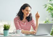 Happy casual beautiful woman working on a laptop at home. poster