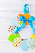 Craft Of Paper In The Form Of A Wreath Of Colorful Paper Eggs On White Wooden Table. Child Does Craf poster
