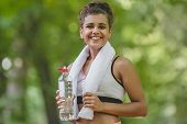 Healthy Woman Runner Have A White Towel On The Shoulder Drinking Water From Plastic Bottle During A  poster