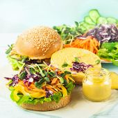 Vegetarian Burger Made From Fresh Sesame Buns And Raw Vegetables And Young Sprouts On A Blue Light B poster