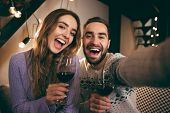 Beautiful happy young couple spending romantic evening together at home, drinking red wine, taking a poster
