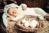 Cute newborn baby lies on a wooden background, dressed in rabbit costume. Easter holiday. Scenery in poster