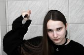 stock photo of serial killer  - Girl with pale face raising a big knife - JPG