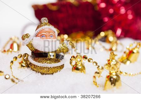 Happy Santa Claus figurine surrounded by Christmas golden bells and snow.