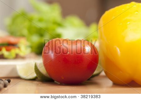 Tomato In The Kitchen Surrounded By Vegetables