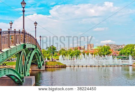 Big Fountain And Green Bridge In Summer Park