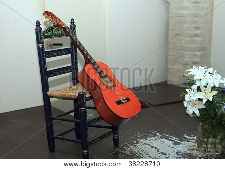 Red Guitar Leaning Against Chair