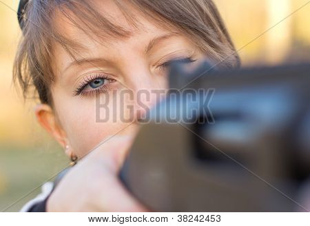 Girl With A Gun For Trap Shooting And Shooting Glasses Aiming At A Target
