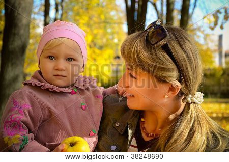 Young Woman Standing In The Park With Her Little Child Holdind An Apple