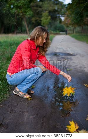 Young Woman Playing An Maple Leaf In Puddle. Autumn Outdoor