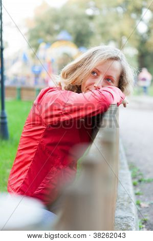Happy Woman Relaxation Leaning On A Wooden Fence. Outdoor