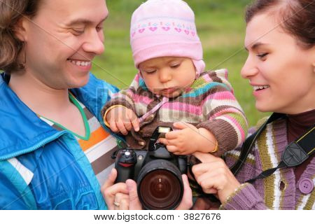 Portrait Of Parents With Baby On Nature With Photocamera