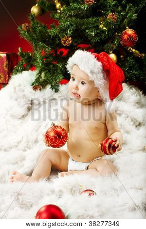 Christmas Baby In Hat Sitting On Fur Holding Red Ball Near New Year Fir Tree