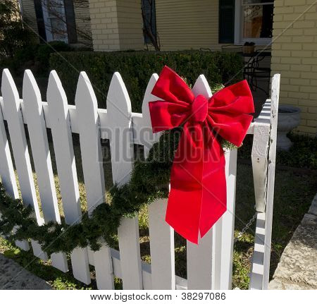 Red Christmas Bow On A White Picket Fence