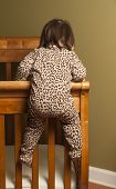 stock photo of bassinet  - Toddler in bedroom climbing out of her crib - JPG