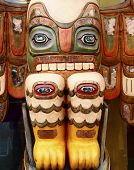 stock photo of indian totem pole  - A totem pole with eyes on knees - JPG