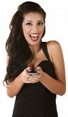 stock photo of overjoyed  - Overjoyed Hispanic woman holding telephone over white background - JPG