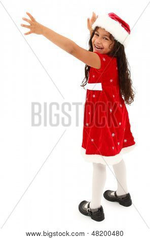 Adorable hispanic preschooler reaching out. Wearing christmas dress and hat. Clipping path.