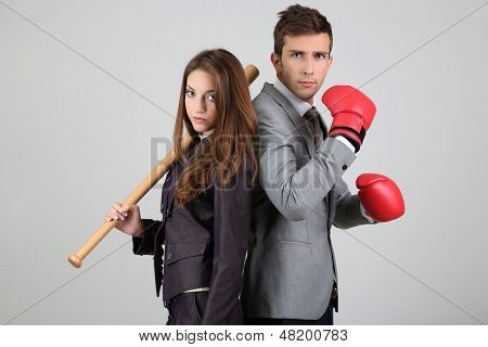 Armed young business people on grey background