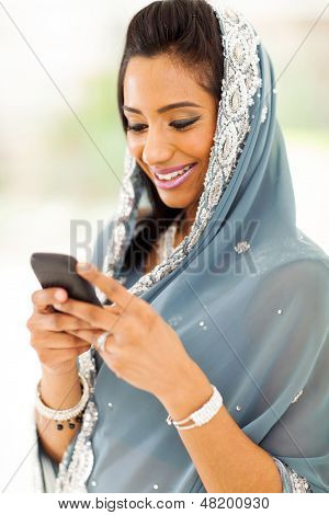smiling indian woman in traditional clothes reading emails on smart phone