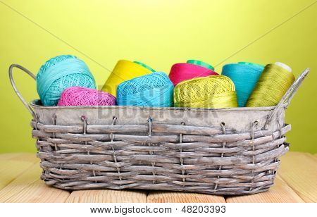 Bright threads in basket on wooden table on green background