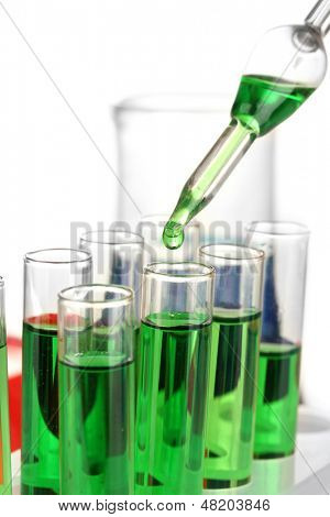 Laboratory pipette with drop of color liquid over glass test tubes, close up, isolated on white