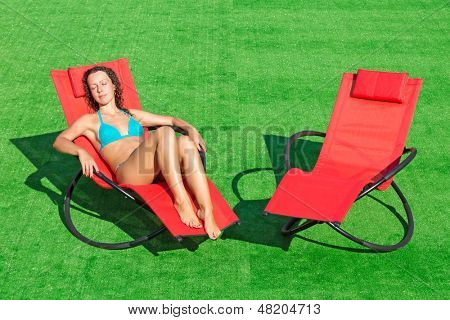 Beautiful girl lying in a deck chair with his eyes closed next to an empty deck chair