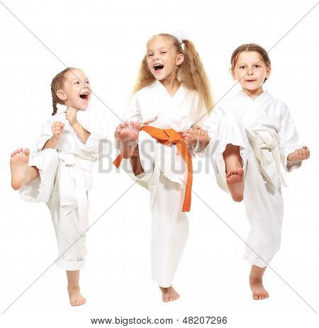Three cheerful girl on a white background in kimono perform a punch leg