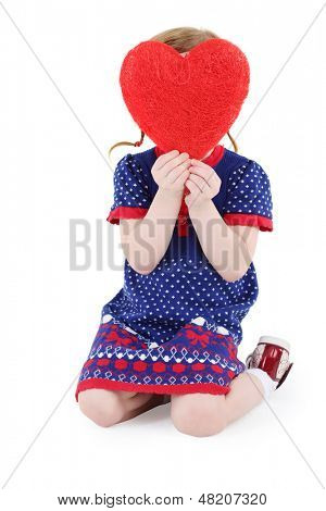 Little beautiful girl sits and hides her face behind red heart at white background.