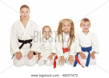 Mother with her daughter and a boy with his sister sitting in a karate pose ritual