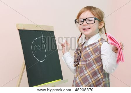 Little happy girl in glasses with pink rag chalk draws face at chalkboard in studio.