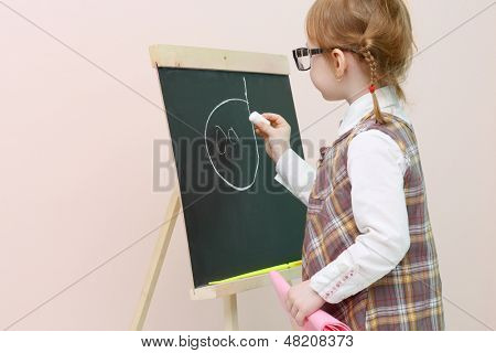 Little girl with red pigtails in glasses chalk draws face at chalkboard in studio.