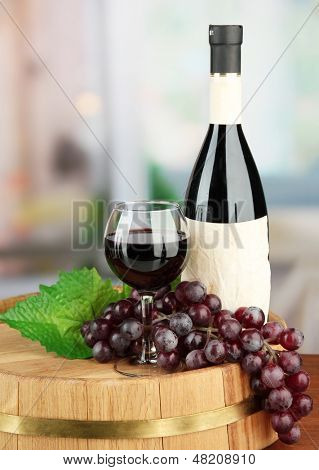 Composition of wine bottle, glass and  grape,on wooden barrel, on bright background
