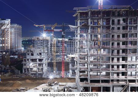 High multi-storey buildings under construction and cranes at night.