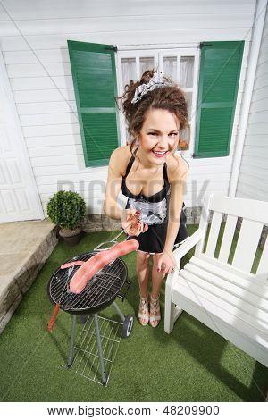 Schöne Hausmädchen Bratwurst auf Kohlenbecken in der Nähe von Haus und hält Bratwurst in Klinge.