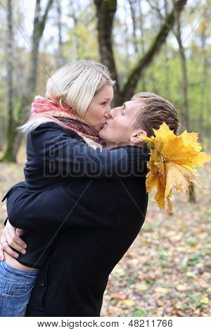 Husband and wife embrace and kiss in autumn forest. Shallow depth of field.
