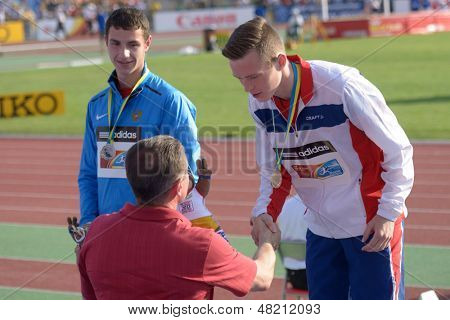 DONETSK, UKRAINE - JULY 12: Medal ceremony in Octathlon boys during 8th IAAF World Youth Championships in Donetsk, Ukraine on July 12, 2013. Ukrainian NOC President S. Bubka (in front) hand off medals