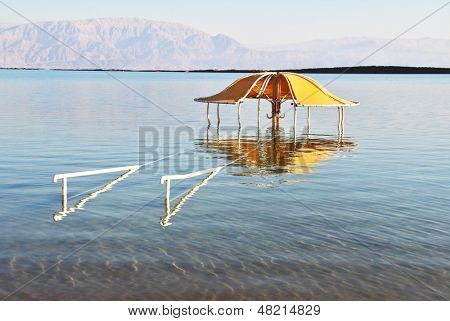 Solar beach on the Dead Sea. Wonderful warm day in December. The beach arbor is half flooded by the risen sea water