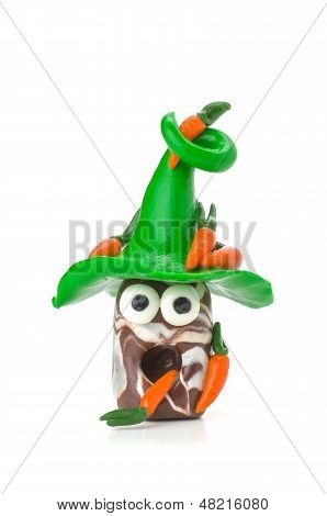Handmade modeling clay figure with carrots on a white background