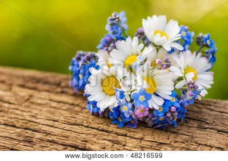 Bouquet with daisies and forget-me-not on a wooden background