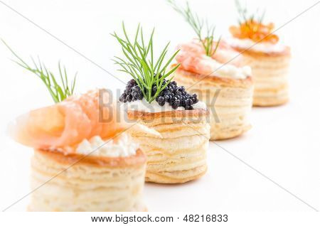Pastries with salmon caviar and shrimp on a white background